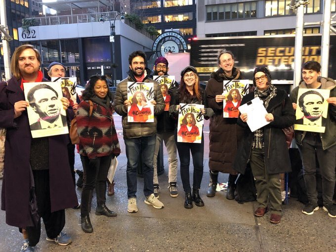 an image of nine activists holding posters of representing incarcerated survivors of gender violence, and Cuomo's face as he is responsible for not freeing them.