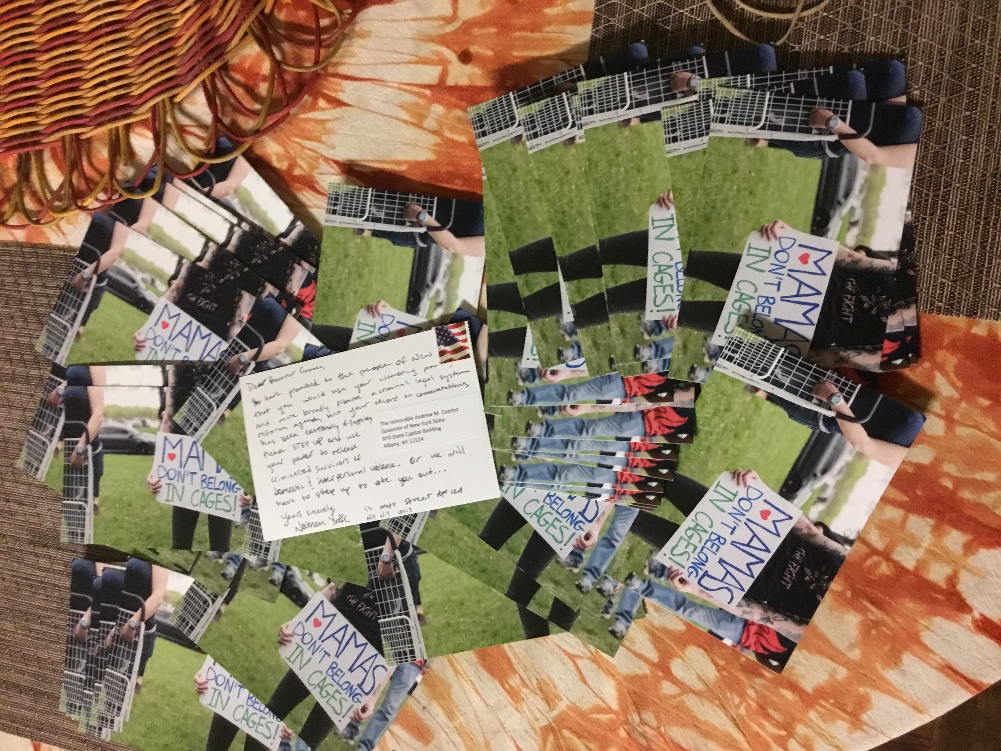 A picture of a large amount of survived and punished postcards in support of our campaign. Each postcard has art on the front including a person holding a sign saying: mamas don't belong in cages. One postcard is turned over to its back, with writing on it addressed to Governor Cuomo urging him to free survivors.